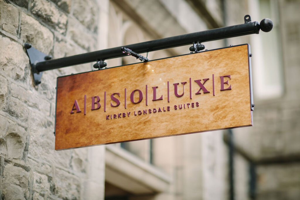 The wooden sign hanging outside the building with Absoluxe engrained on it
