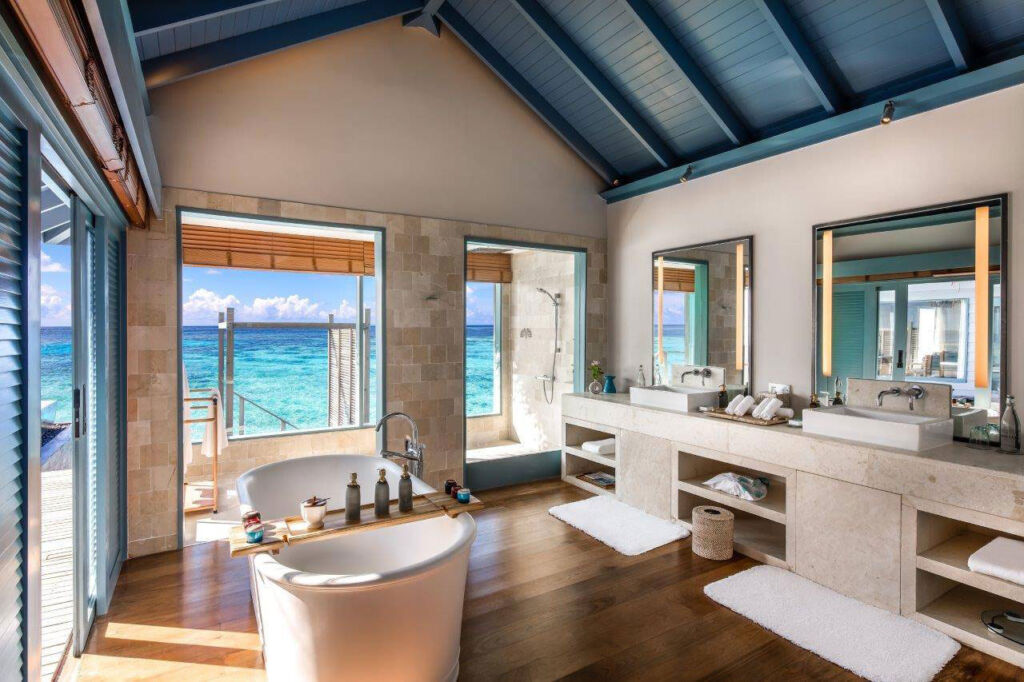 A beautiful bathroom in an overwater villa with large windows looking out over the blue sea