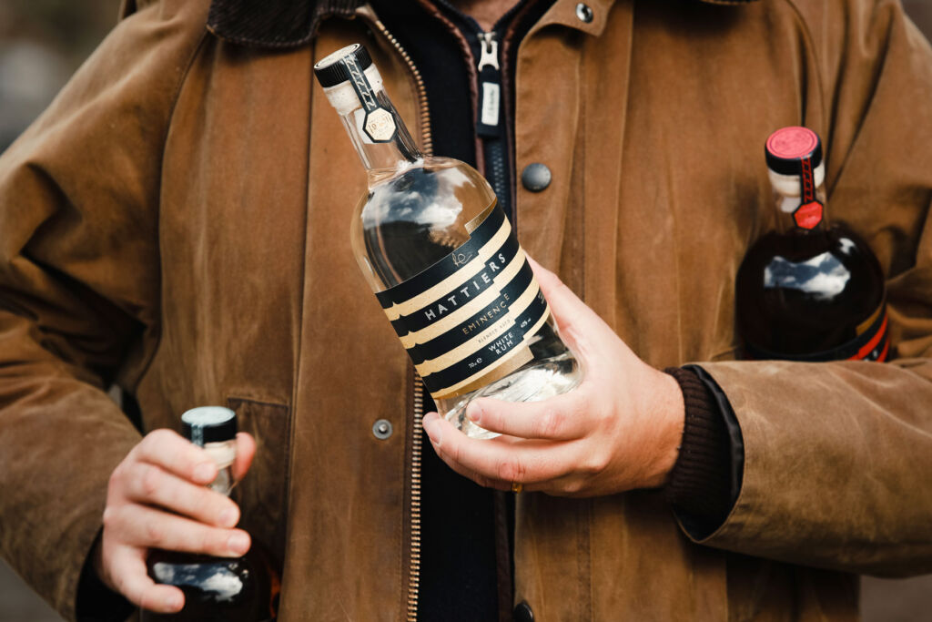 A man carrying a few bottles of Hattiers Rum