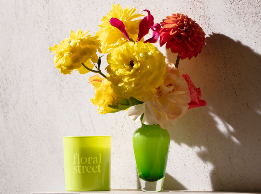 A scented candle next to a vase filled with fresh yellow flowers