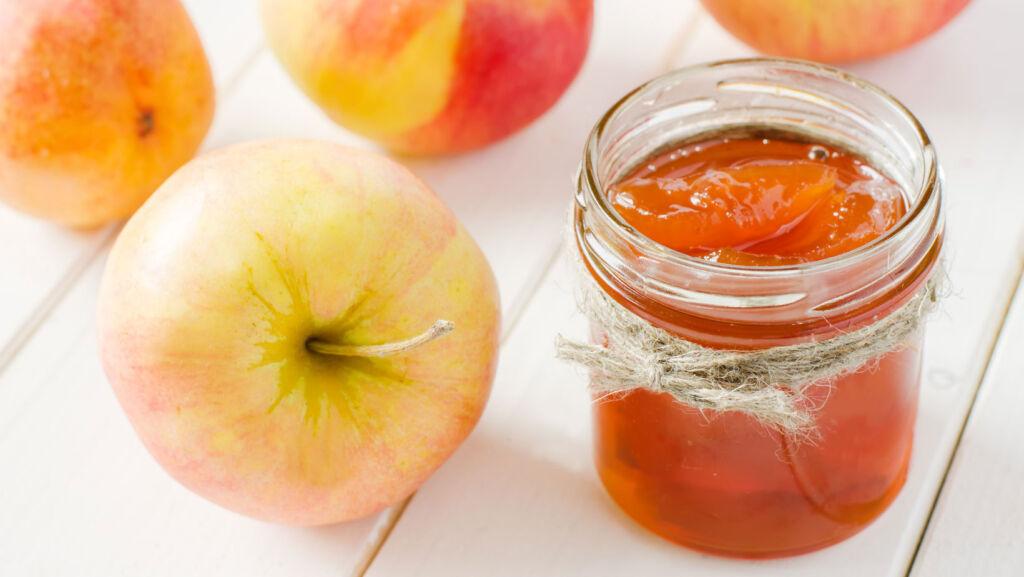 A jar of homemade apple jam alongside some fresh apples