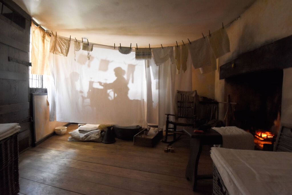 The silhouette of a housemaid being projected into a hanging sheet