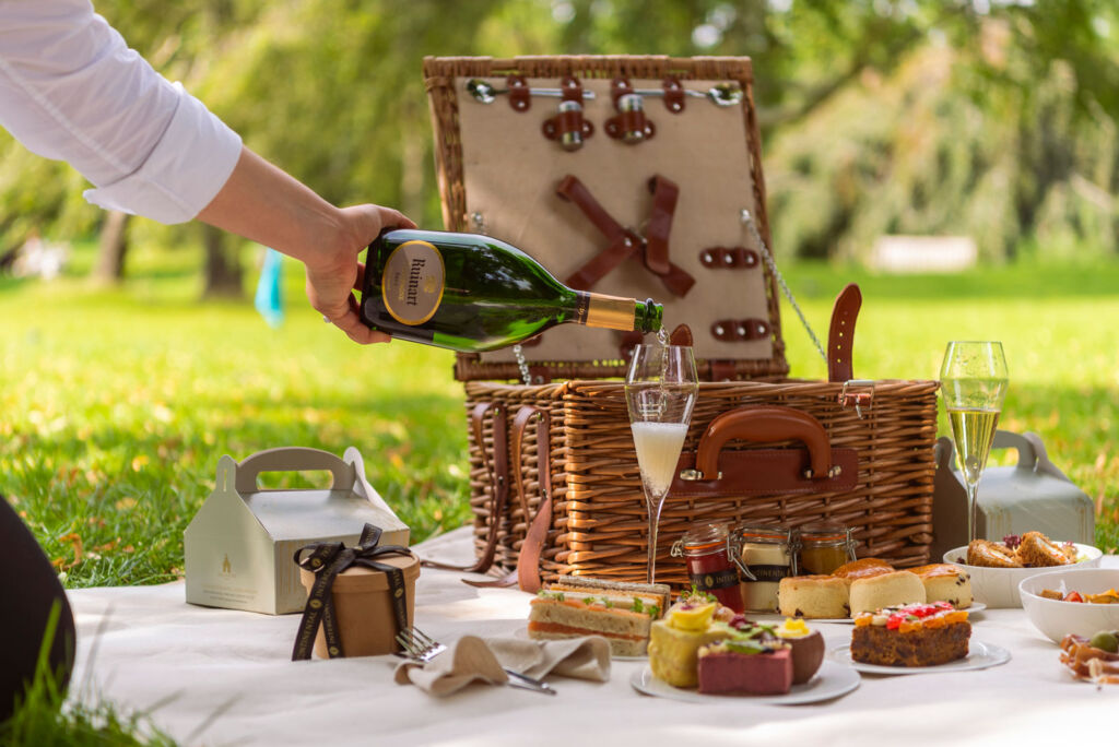 Someone pouring a glass of bubbly with their exceptional picnic hamper
