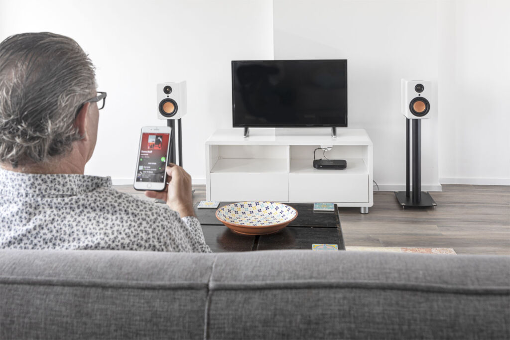 A man listening to his favourite music tracks via his mobile phone on the speakers