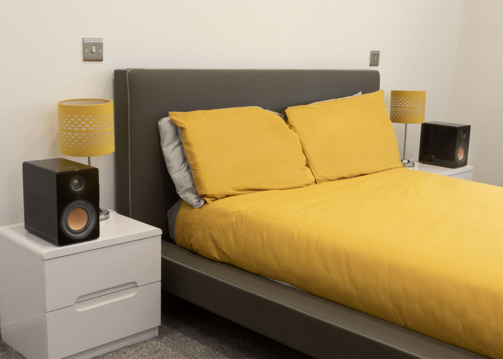 A pair of the speakers in piano black gloss sat aside a large bed on cabinets