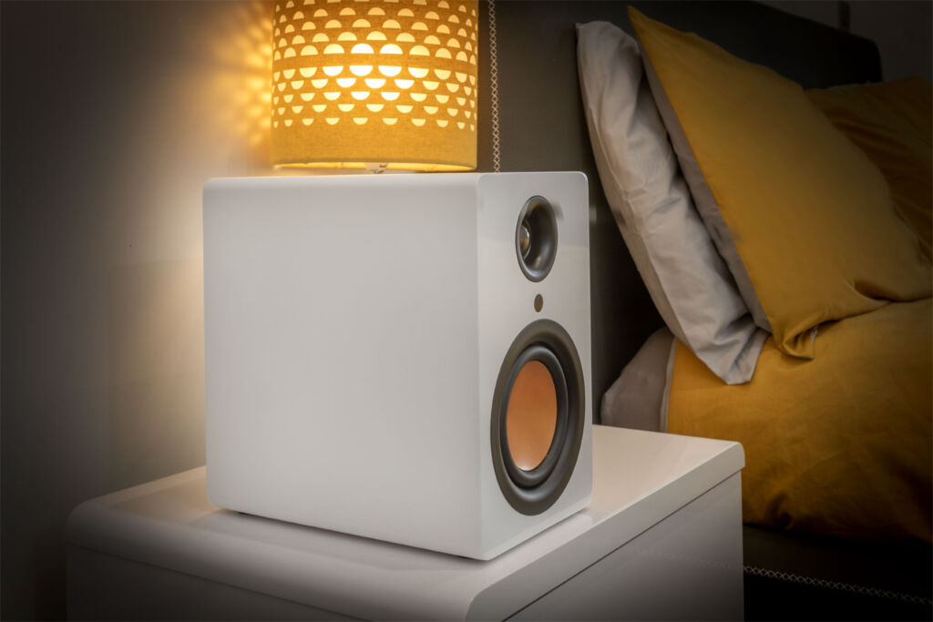 One of the speakers sat upon a bedside cabinet