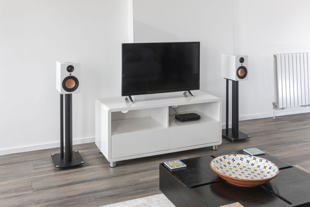 A set of the speakers mounted on stands either side of a television