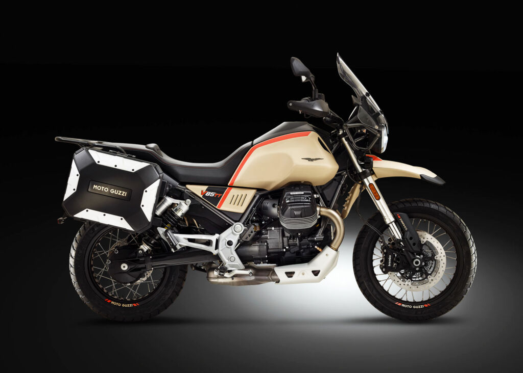 A side view of the motorcycle in a cream livery with red accents