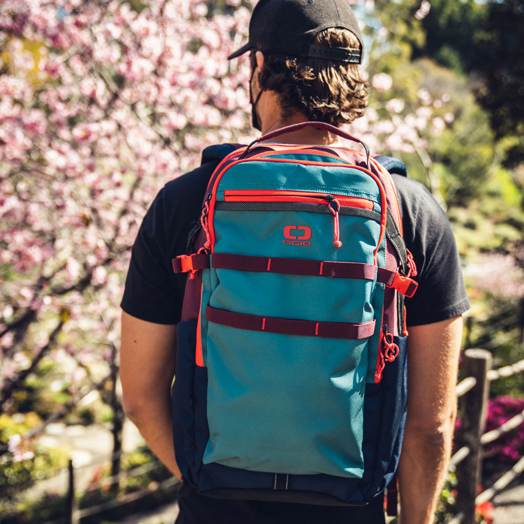 An Ogio Alpha+ Backpack in blue being worn by a man