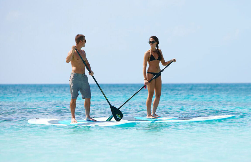 A man and a woman paddle boarding on the sea