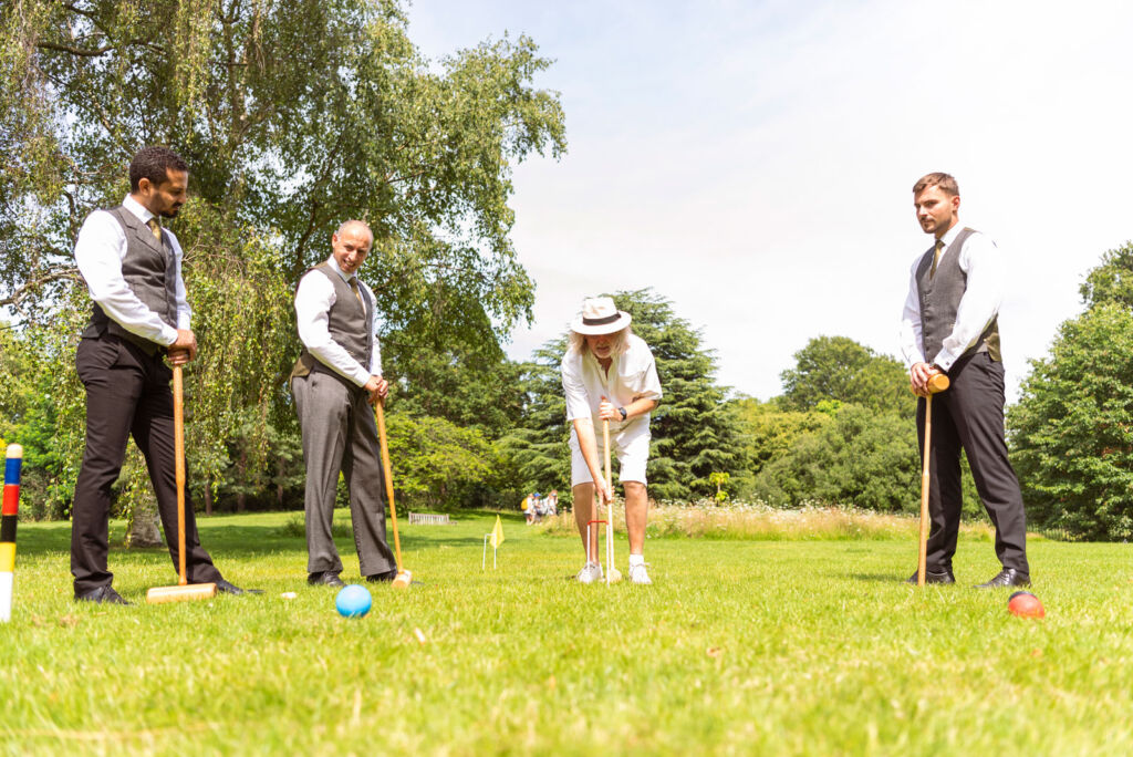 Staff being trained in the sport of croquet