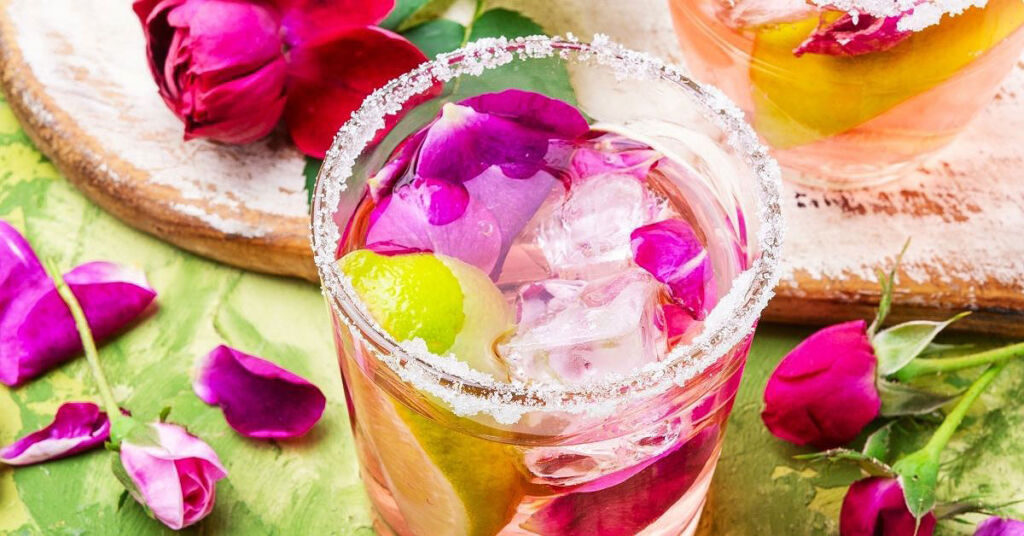 A beautiful glass of rosewater iced tea with ice and petals floating in it