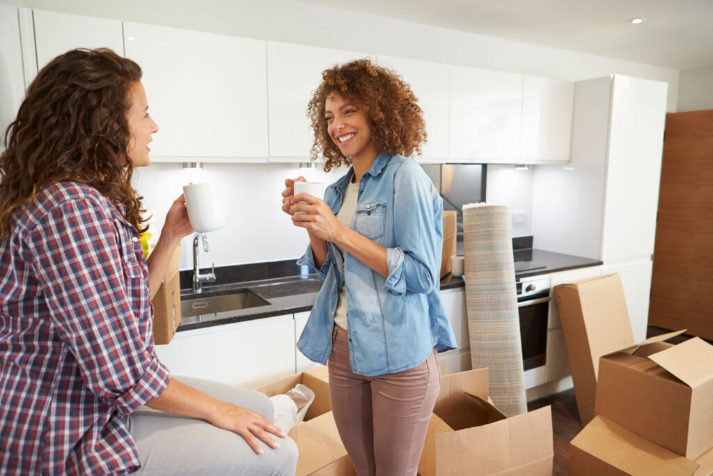 Two women relaxing in their new home surrounded by cardboard boxes