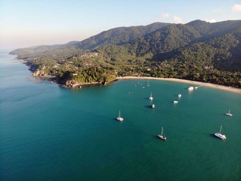 Boats moored off the shore in front of the Pimalai Resort & Spa in Koh Lanta Thailand
