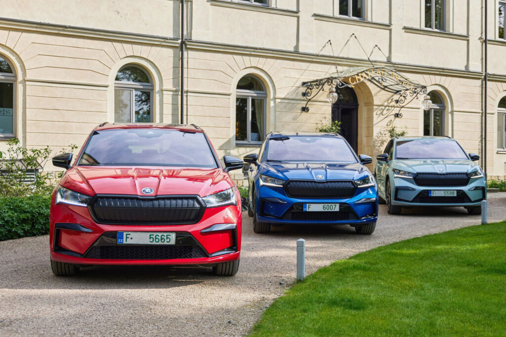Three Enyaq's in different colours parked outside a stately home