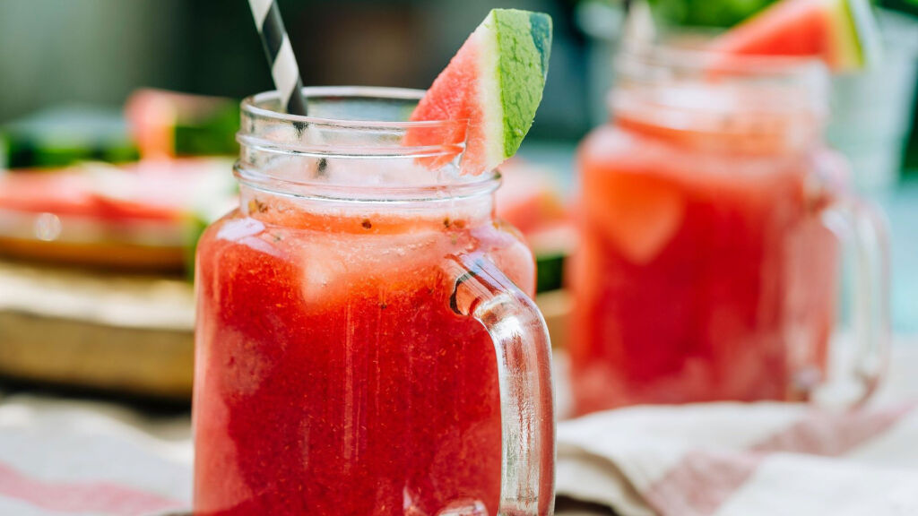 A small jug of watermelon iced tea with a striped straw and a slice of watermelon on the rim of the glass