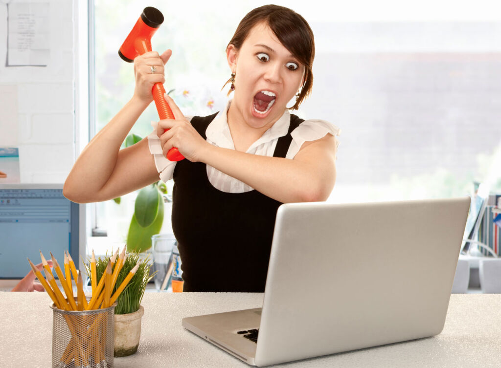 A young woman ready to smash her notebook with a hammer