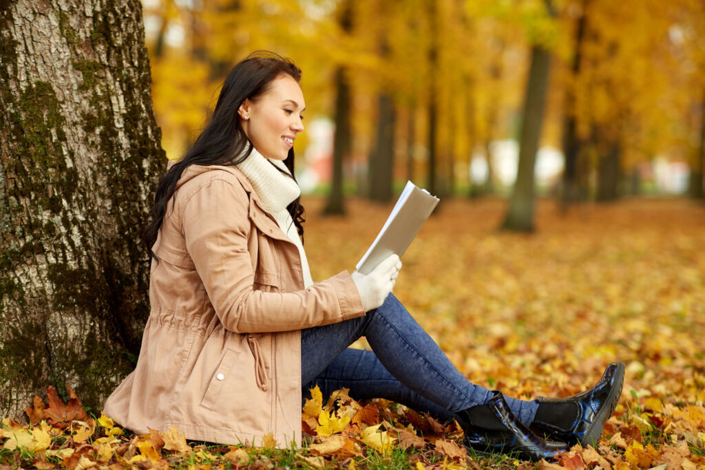 A young woman reading a book in a forest