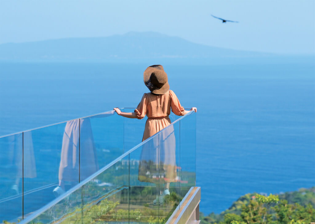 A woman standing on a glass walkway admiring the view over the coast and sea