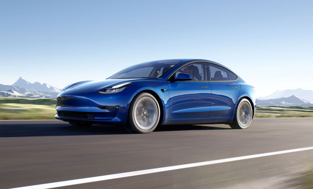 Blue Tesla being driven a speed on the road