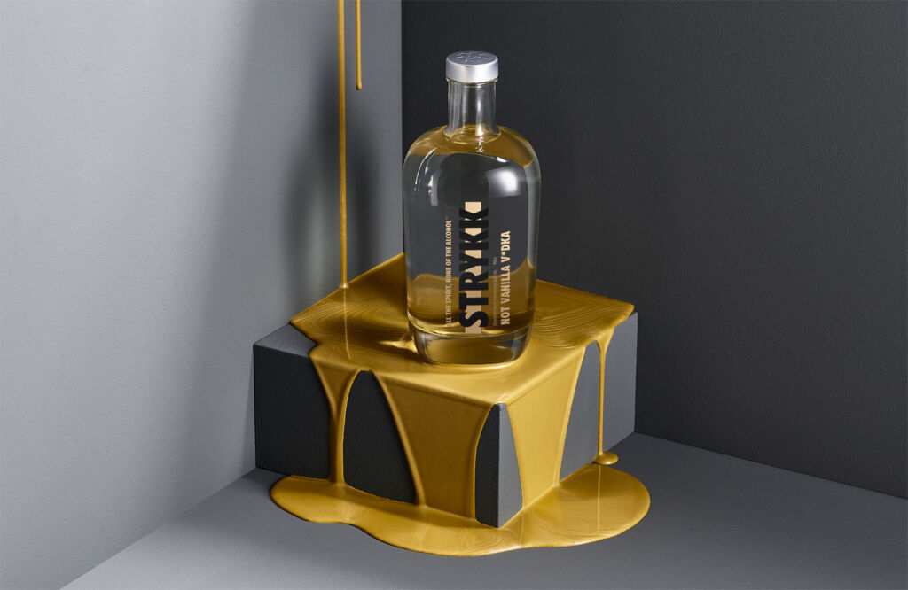 A bottle of the Not Vanilla Vodka drink sitting on a box dripping with yellow paint