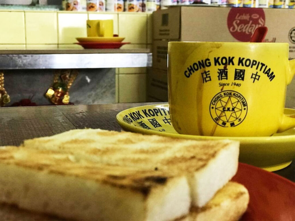Breakfast at Chong Kok consisting of a bright yellow mug of coffee and slices of thick toast