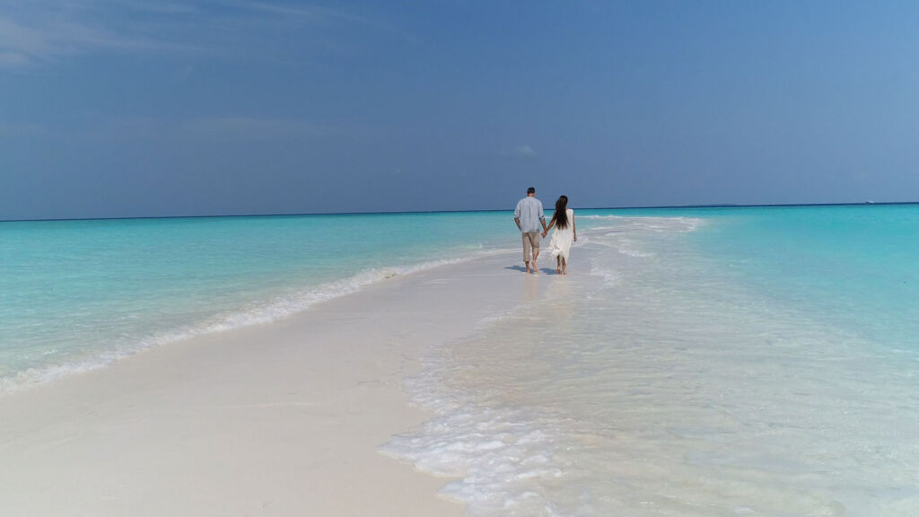 A couple taking a romantic stroll on the beach