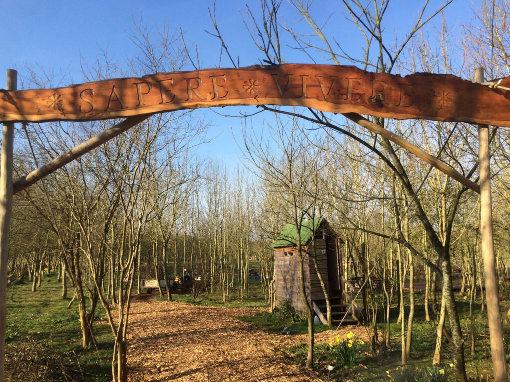 The entrance to the glamping site with the word Sapere Vivere carved above it, meaning live the life