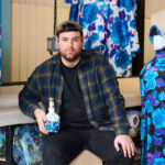 Designer Richard Quinn holding a bottle of the Royal Salute Whisky