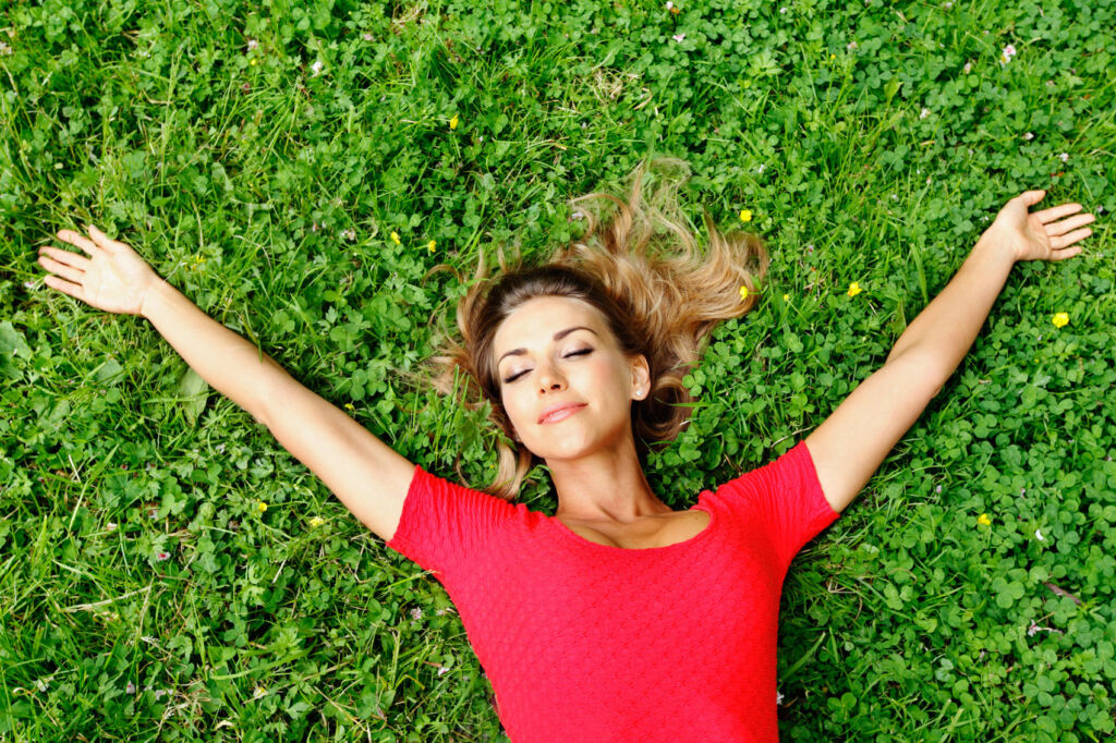 A happy young woman laying on her garden knowing shes helping to reduce food waste