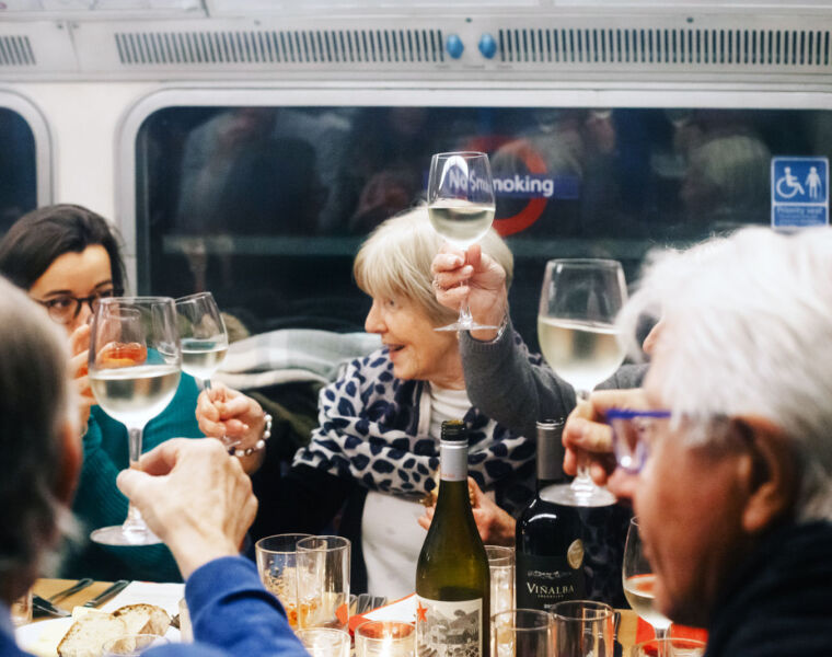 People raising a glass on London's Supperclub Tube restaurant