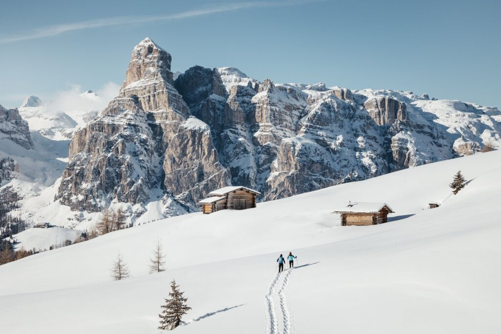 A couple walking towards a hut on the snow capped mountains