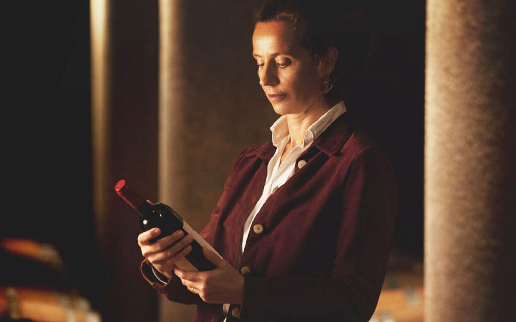 Ilaria in her cellar examining a bottle of wine