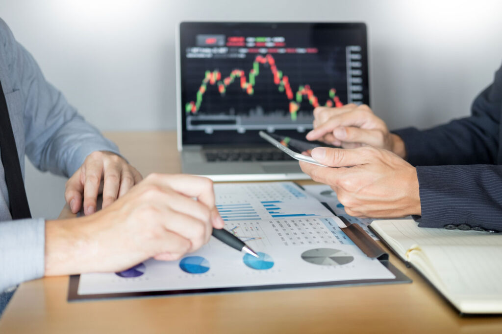 Two people discussing investments over a desk