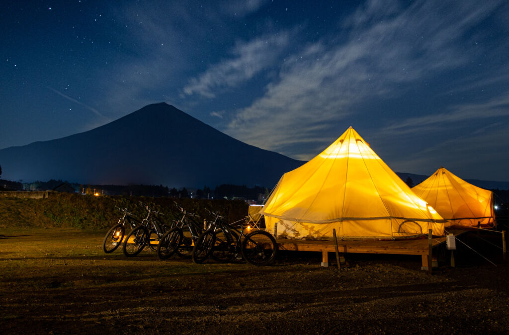 Mount Fuji looming in the background, lit by the glow of the luxury tented accommodation