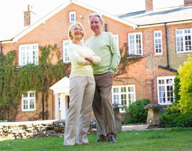 An older couple enjoying their retirement outside their Georgian styled dream home