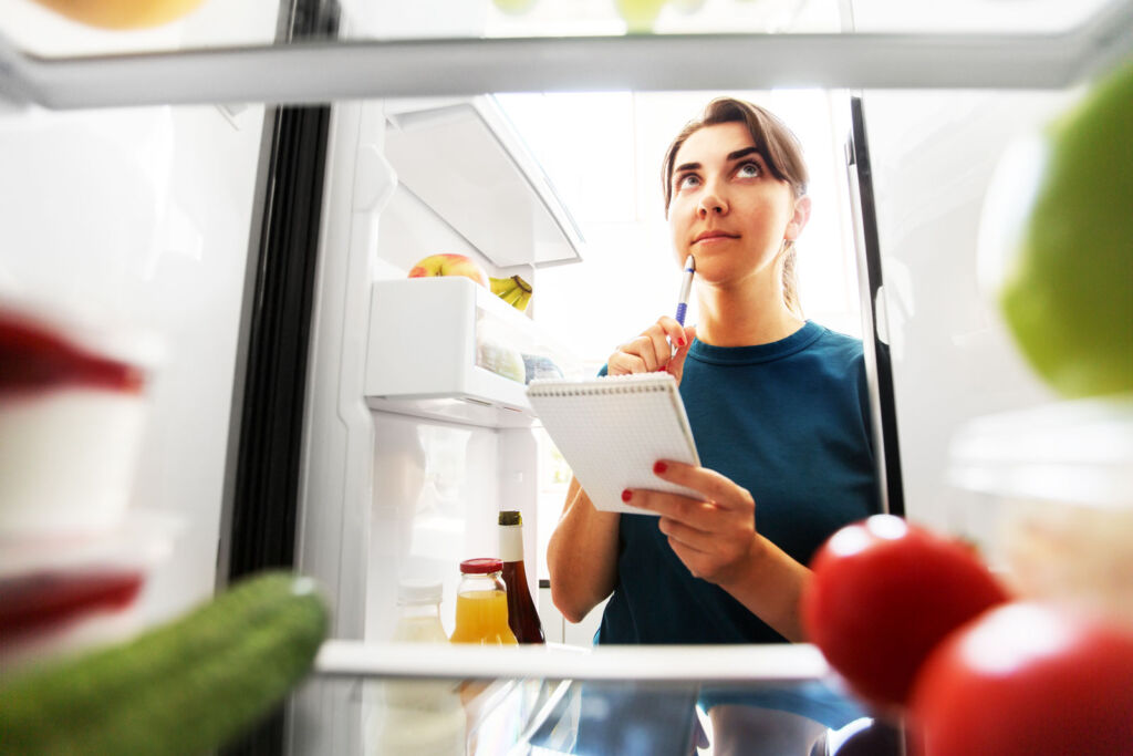 A young woman organising the contents of her fridge