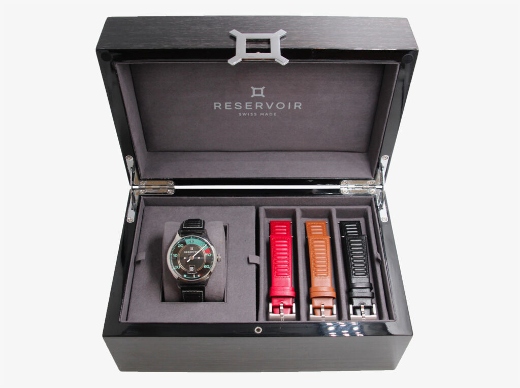 The watch in its box with the range of different coloured extra straps