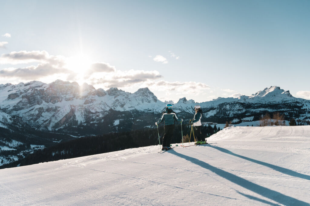 A couple ready to ski down a perfectly prepared slope