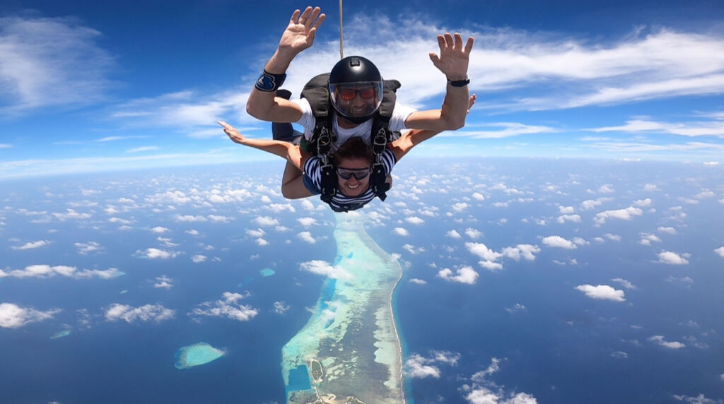 A lady skydiving with an instructor high above the private island