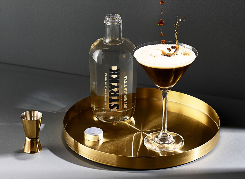 An espresso Martini cocktail sat on a gold tray
