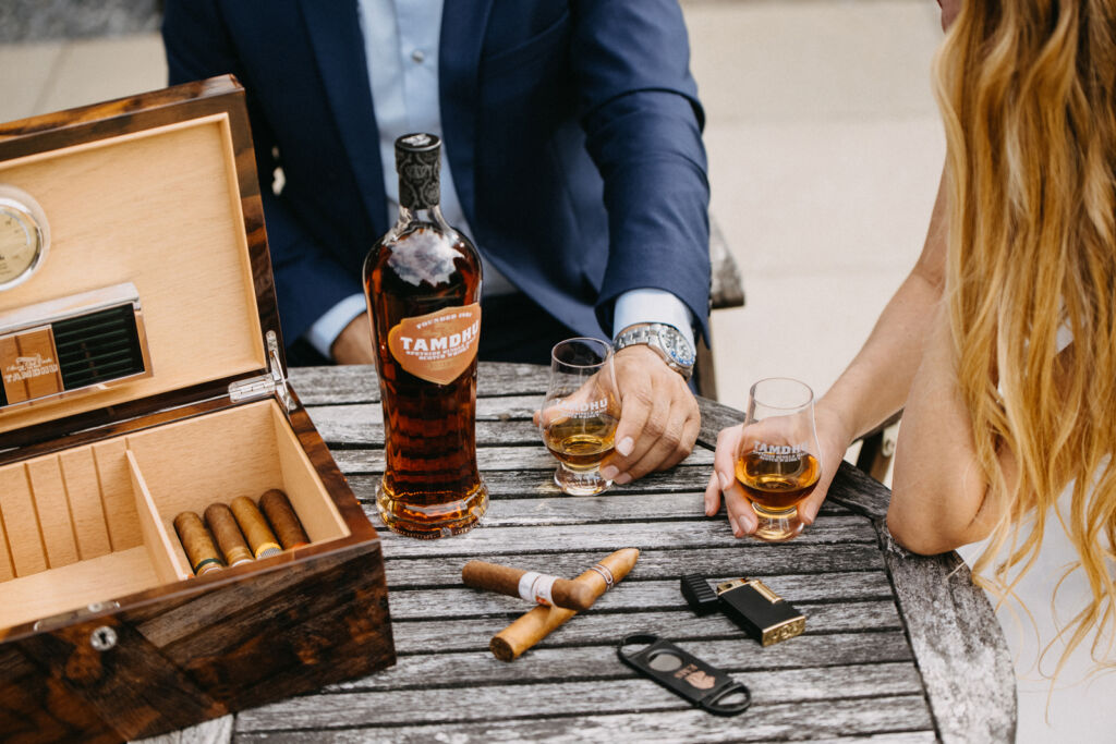 A couple enjoying a bottle of the whisky, which is next to the luxury humidor