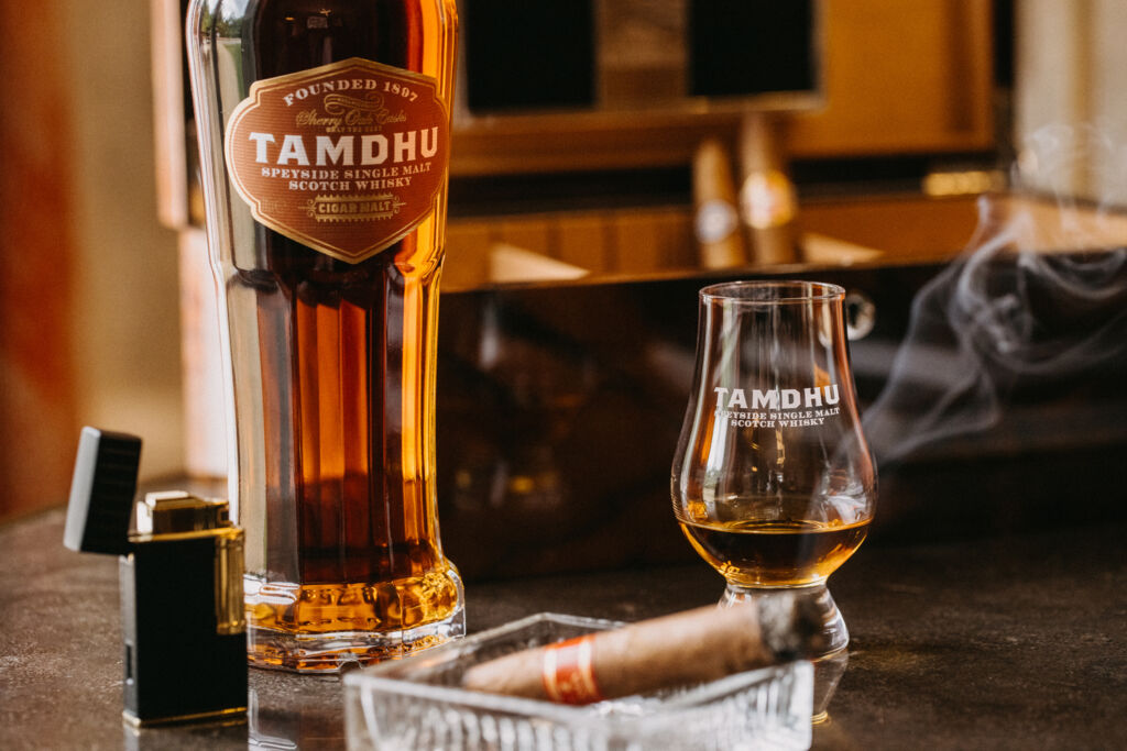 A glass of Tamdhu whisky being enjoyed with a fine cigar