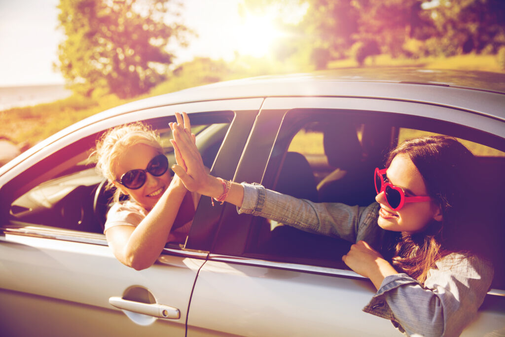 Two ladies sharing a happy experience in a car