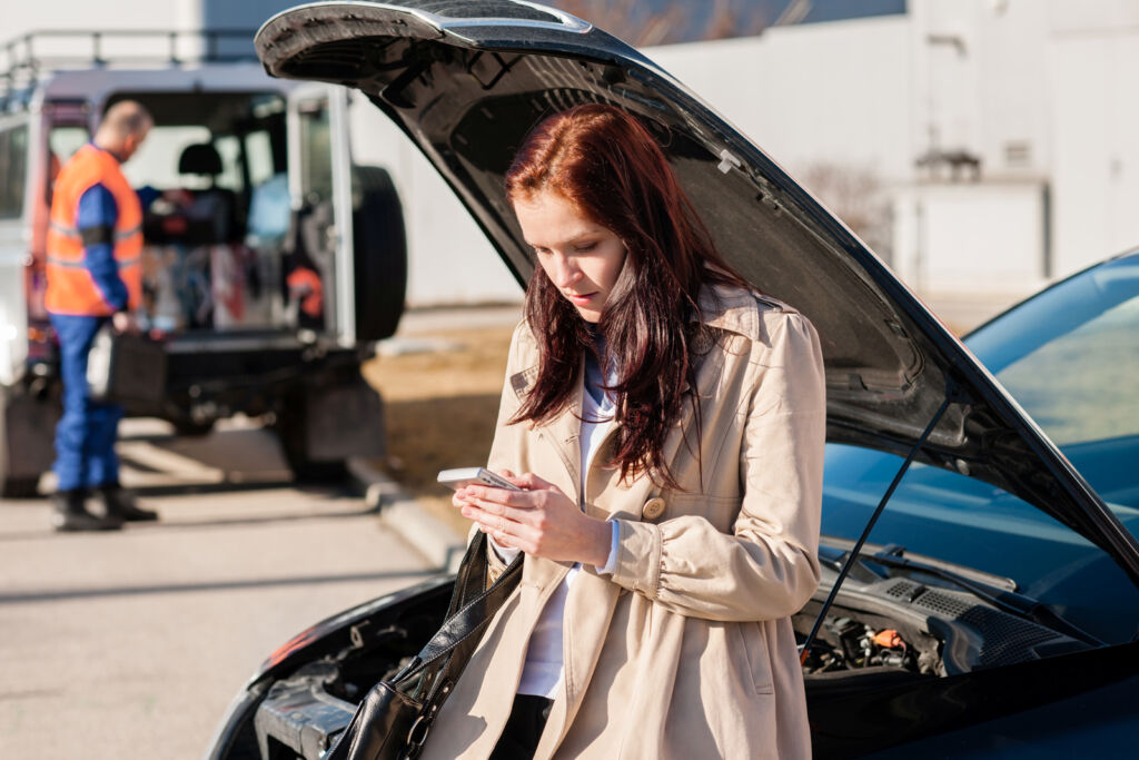 Young woman realising she's put the wrong fuel in her car, and calling for professional assistance