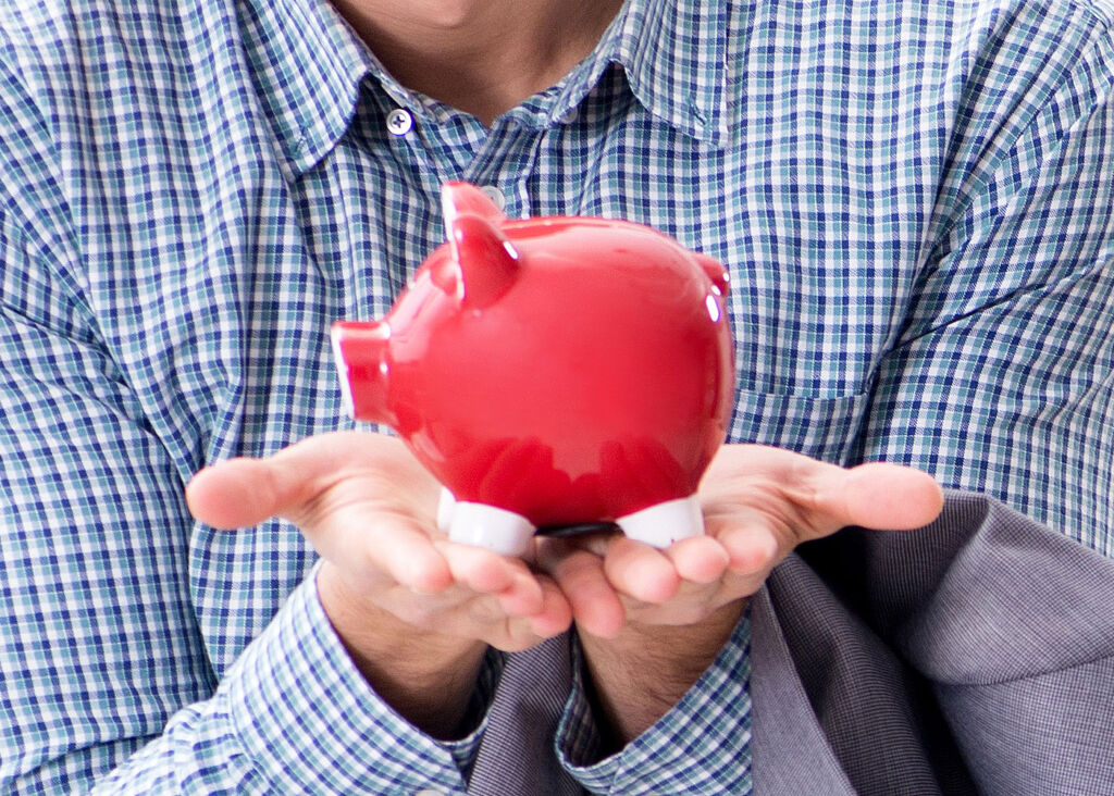A young person holding a full piggy bank