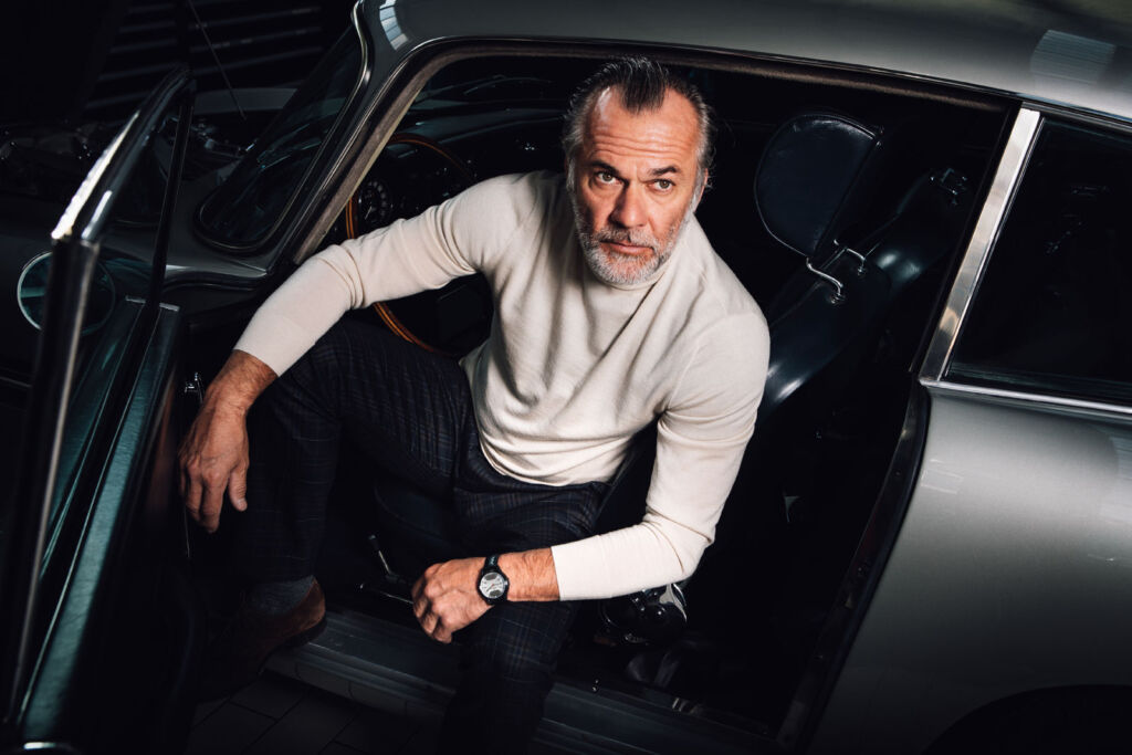 An older bearded male model wearing one of the timepieces in a silver Aston Martin DB5