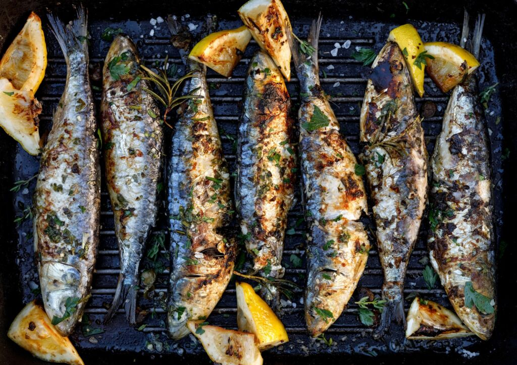 Sardines being cooked on a BBQ