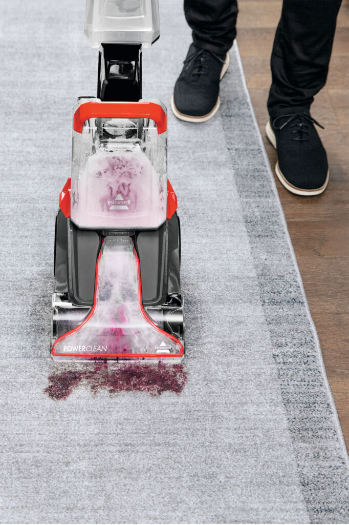 The carpet cleaner being used to clean up some spilled wine