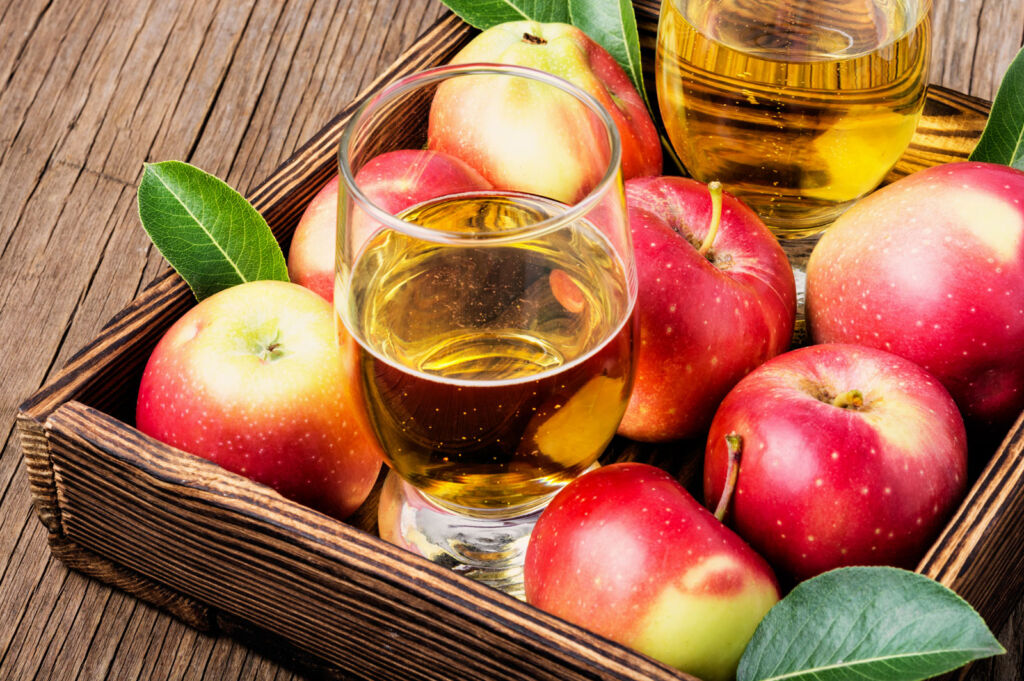 Some fresh red British apples with glasses of apple juice in a tray